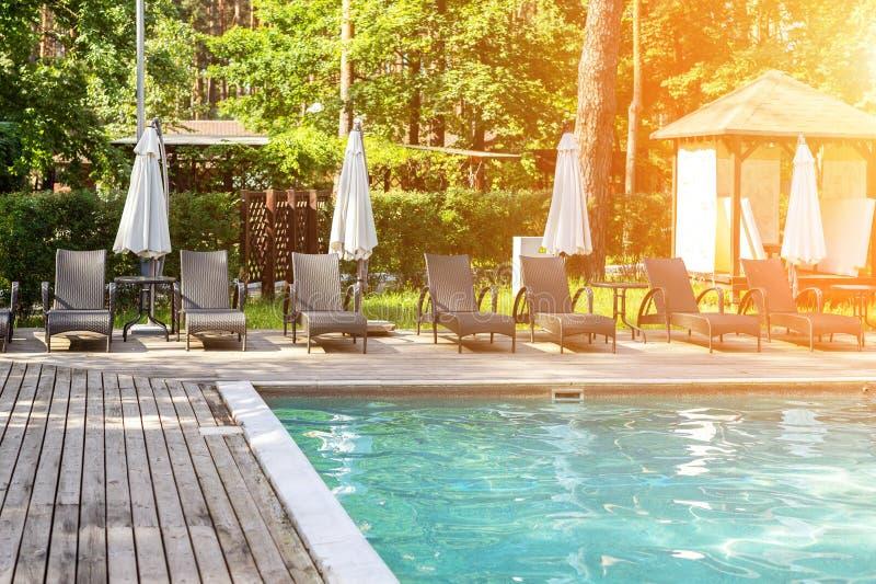 Poolside con chiare acqua blu e chaise-lounge sotto gli ombrelli su calore di giorno di estate Piscina alla località di soggiorno fotografia stock