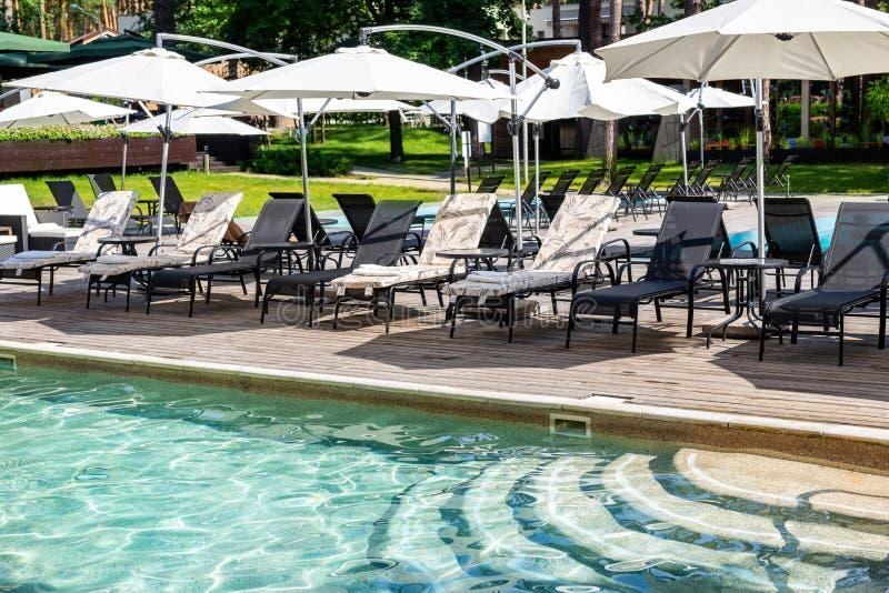 Poolside con chiare acqua blu e chaise-lounge sotto gli ombrelli su calore di giorno di estate Piscina alla località di soggiorno fotografia stock libera da diritti
