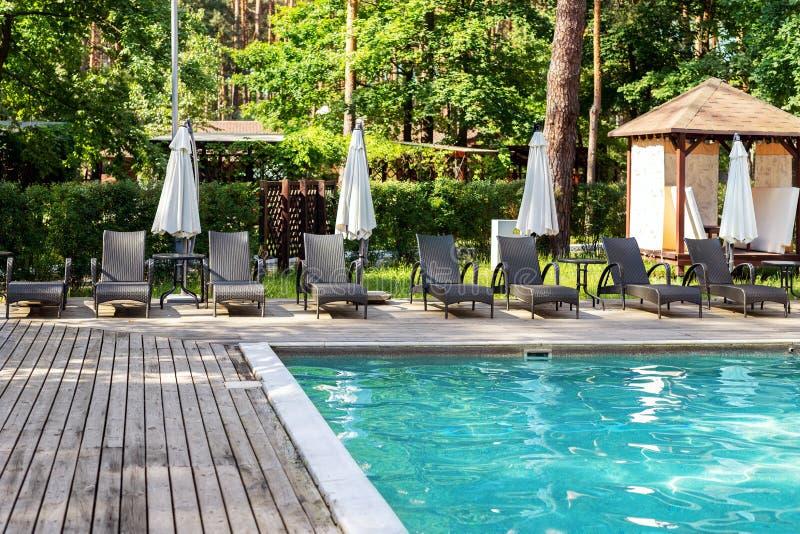 Poolside con chiare acqua blu e chaise-lounge sotto gli ombrelli su calore di giorno di estate Piscina alla località di soggiorno fotografie stock