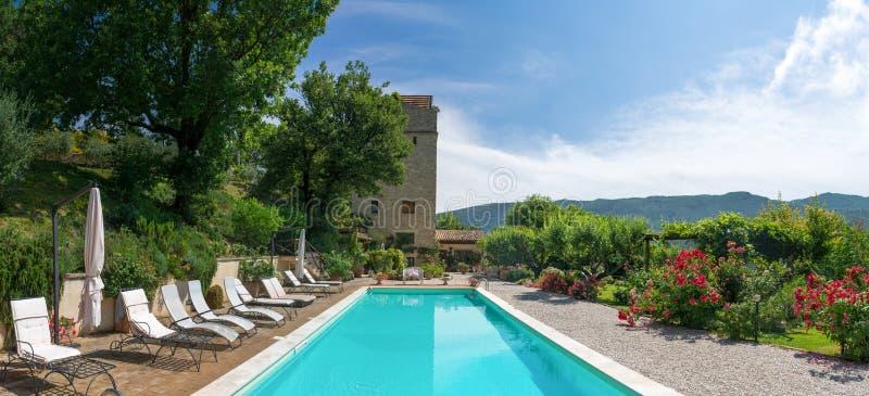 Poolside en la piscina clásica de la mansión y jardín que mira la torre imágenes de archivo libres de regalías