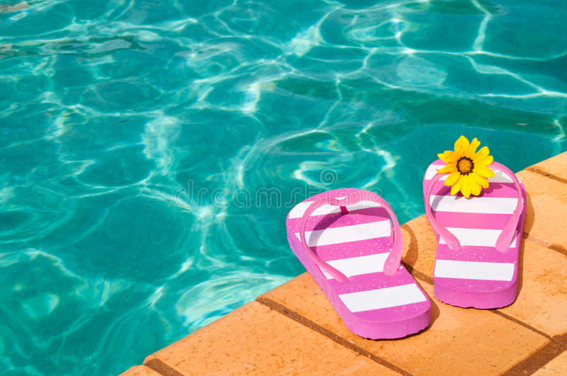 Poolside Flip Flops. Colorful summer flip flops by the side of luxury swimming pool with flower royalty free stock photos
