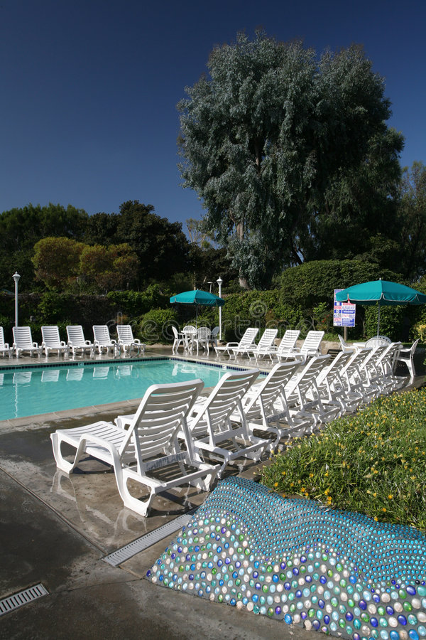 Poolside with Lounge Chairs stock images