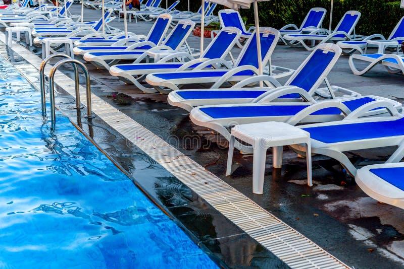 Poolside mit blauen chezlongs und Poolabschluß herauf Ansicht lizenzfreie stockbilder