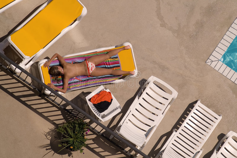 Poolside que toma el sol fotografía de archivo libre de regalías