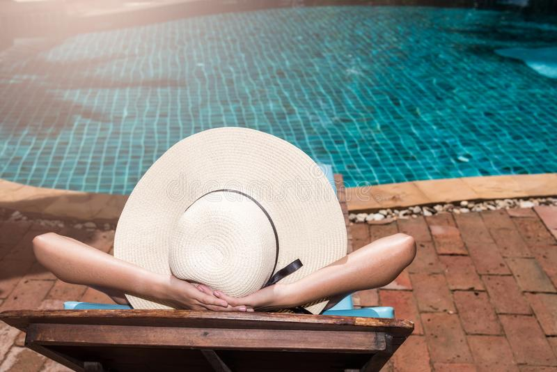 Poolside relajante asiático del sueño de las mujeres jovenes en el poo de lujo de la natación imágenes de archivo libres de regalías
