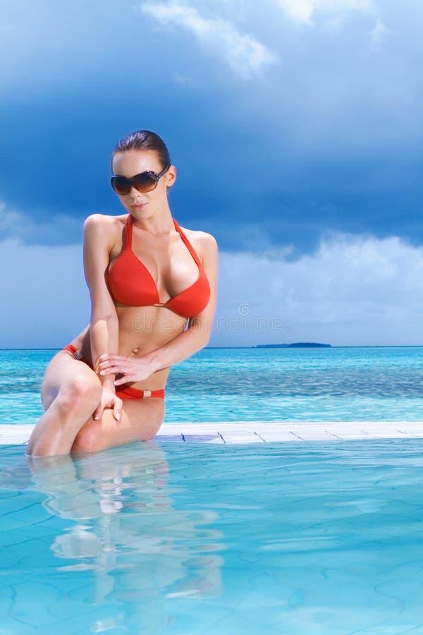 Poolside relajante de la mujer atractiva foto de archivo