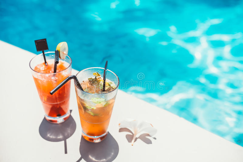 Poolside symmetric cocktails served cold at pool bar with mojito and gin and tonic lemonade stock images
