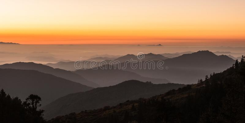 Poonhill view of mountains around Annapurnas. Warm pink and orange sunrise light over Annapurna mountain range with blue sky stock photo