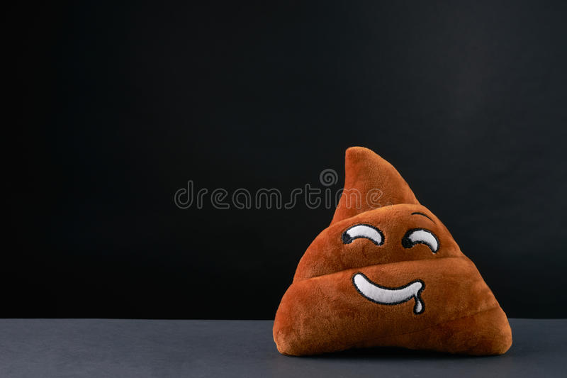 Poop emoticon. On black background with copy space royalty free stock photos
