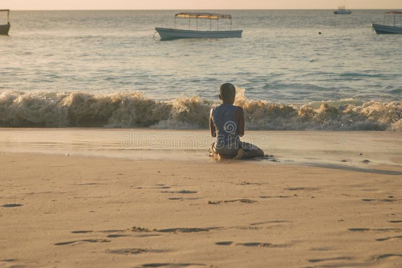 Poor African-American child playing on shore of ocean. Poor African-American child playing on the shore of the ocean royalty free stock images