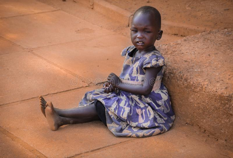 A poor African girl begs for alms in the capital Kampala royalty free stock photography