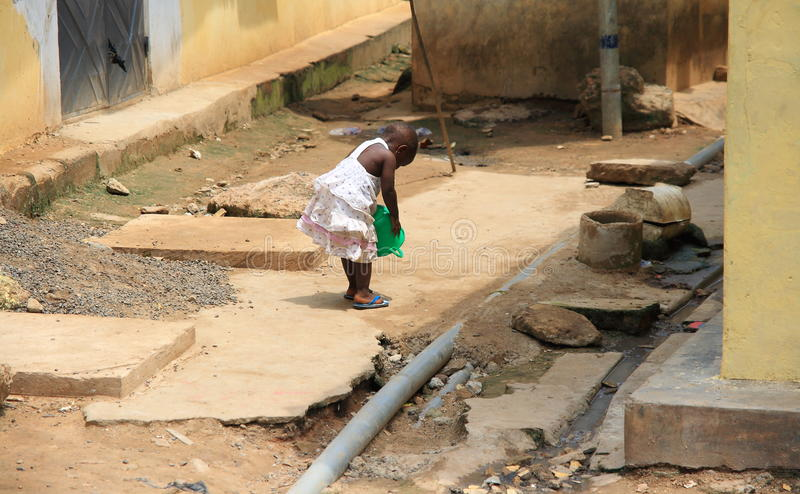 Poor African girl playing in front of her house royalty free stock image