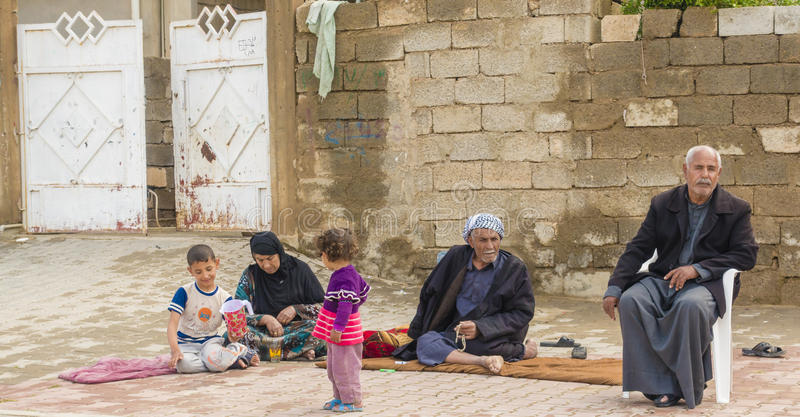 Poor Arab family. Kirkuk, Iraq - October 26, 2015: Poor Iraqi people sitting in front of them house in township in Iraq stock photography