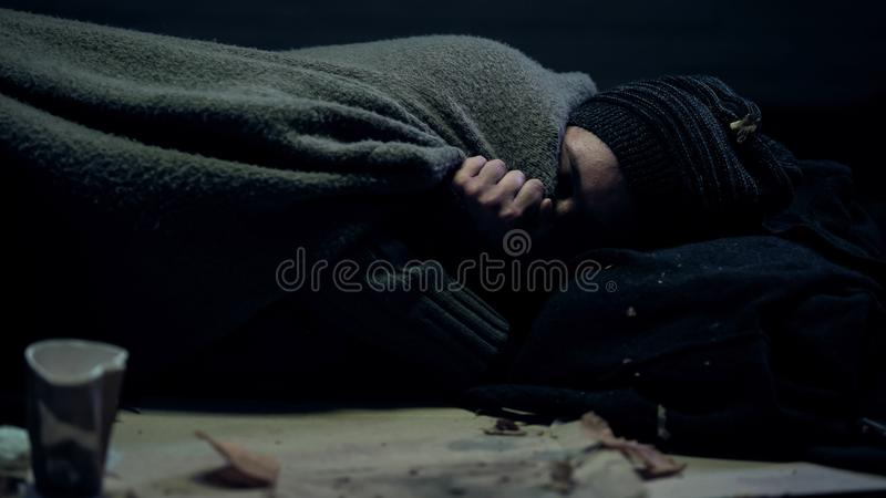 Poor beggar covered dirty blanket sleeping on street feeling cold, homelessness. Stock photo royalty free stock photo