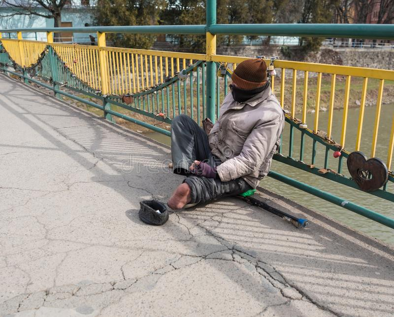 Poor beggar without leg asking for alms royalty free stock photo