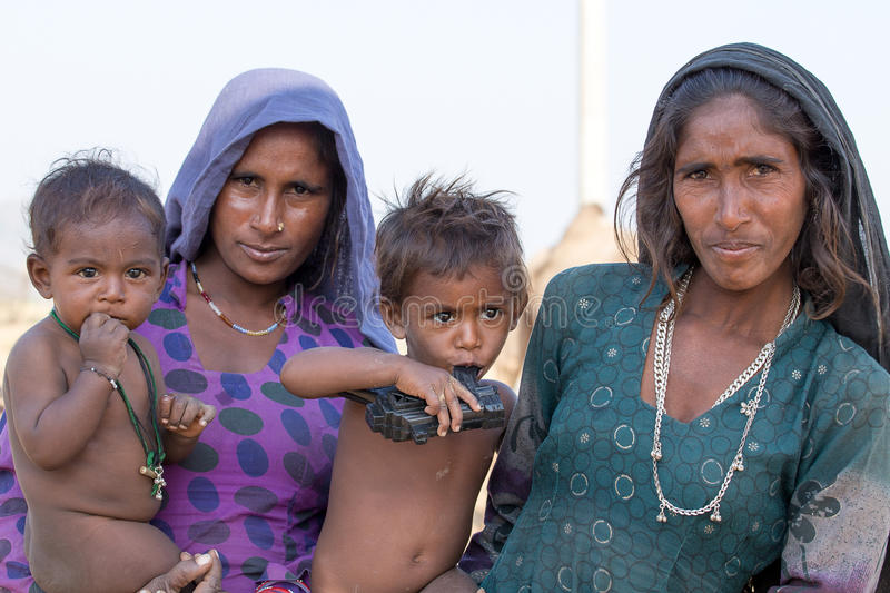 Poor beggar women and children begs for money from a passerby in Pushkar. India royalty free stock image