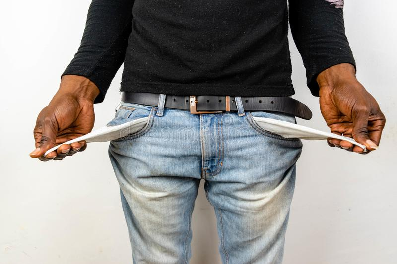 Poor Black man in jeans with empty pocket. Nigerian African American Man showing empty denim pockets on white background for joble stock photography