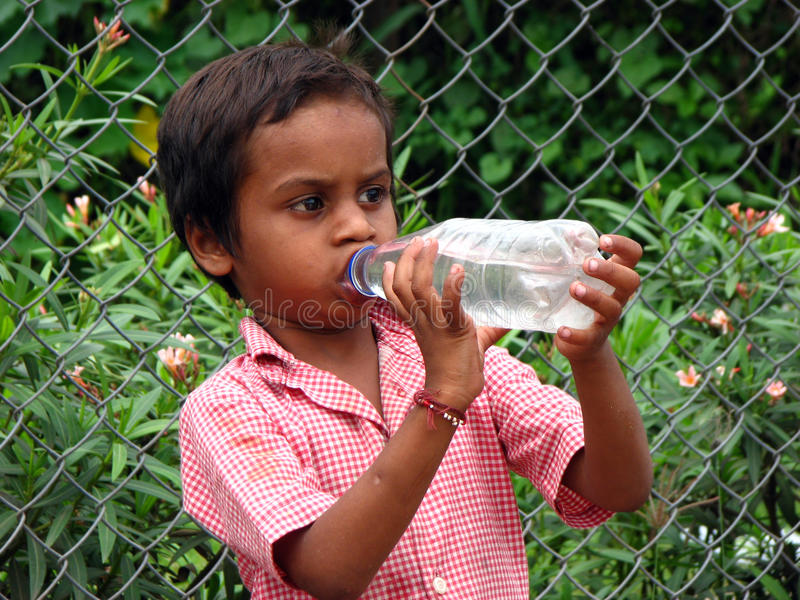 Poor Boy Drinking Water. A poor Indian boy drinking water from a bottle stock image