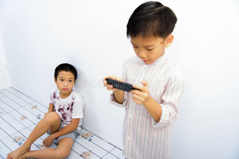 Poor boy and smartphone. Younger Asian boy play smartphone, another poor boy looks interest at phone at the white wall. Social network concept stock photography