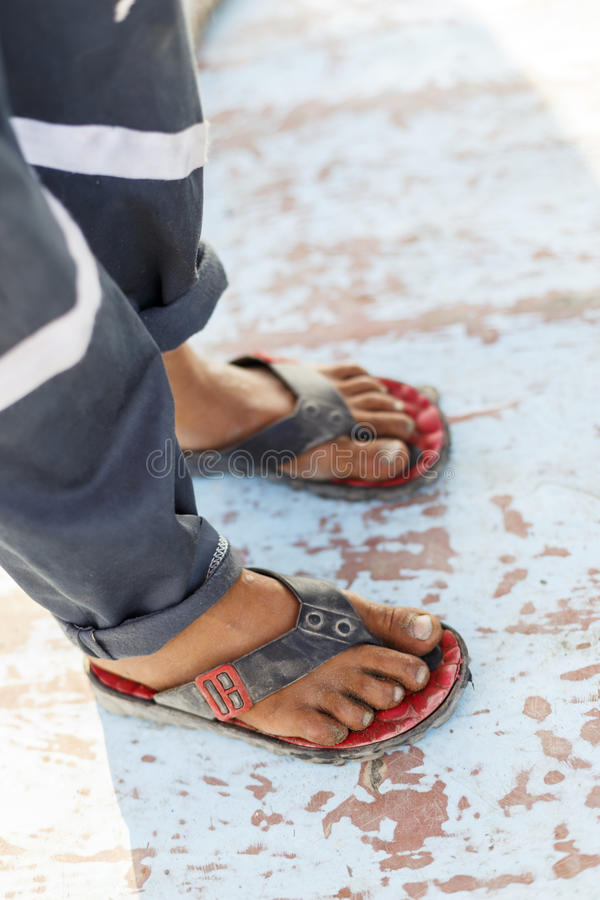 Poor boy wearing flip-flops. Daylight stock photography