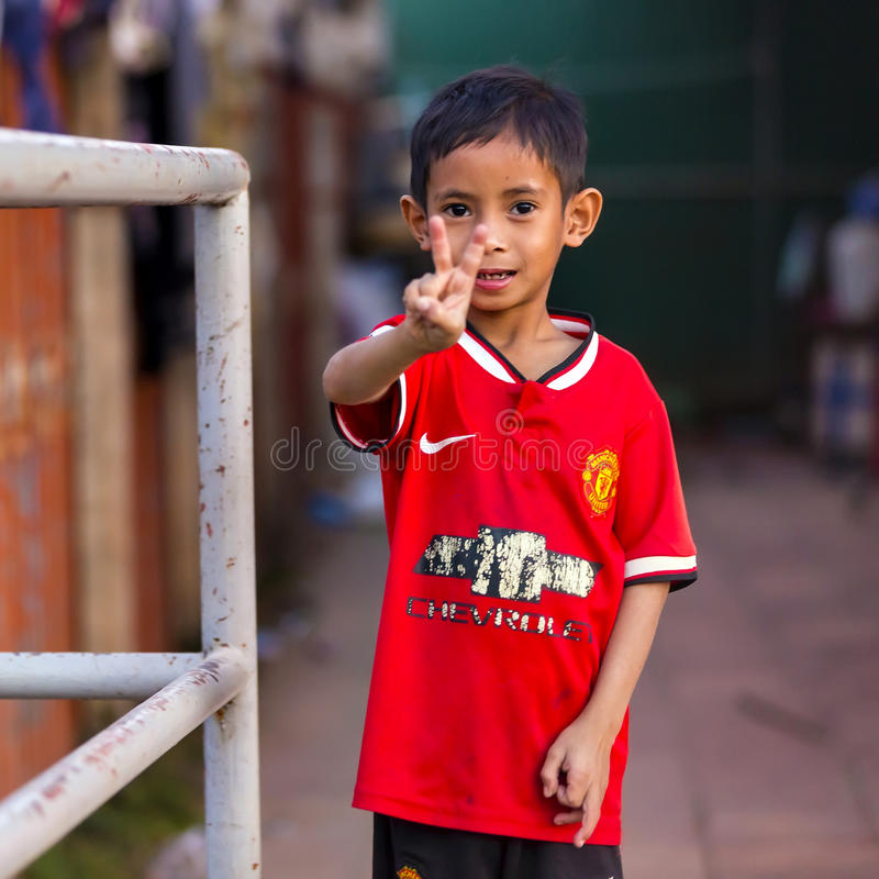 Poor Cambodian boy shows victory sign stock photos