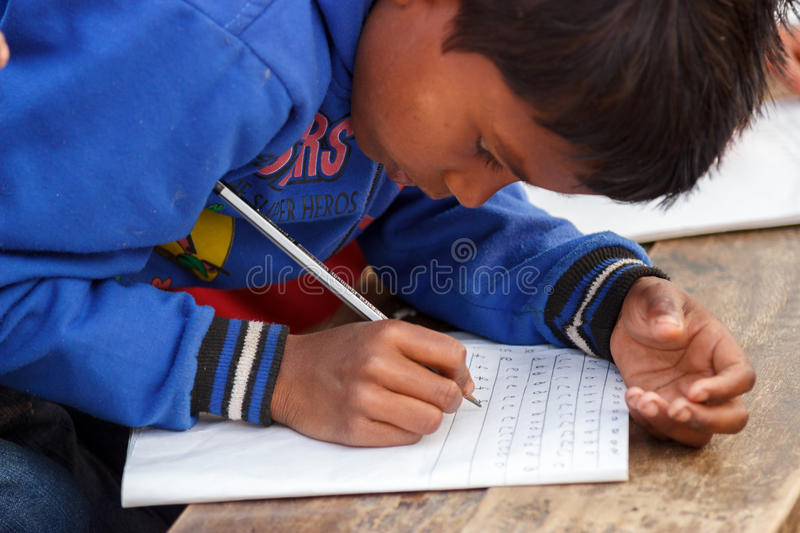 Poor child learning, writing stock photos