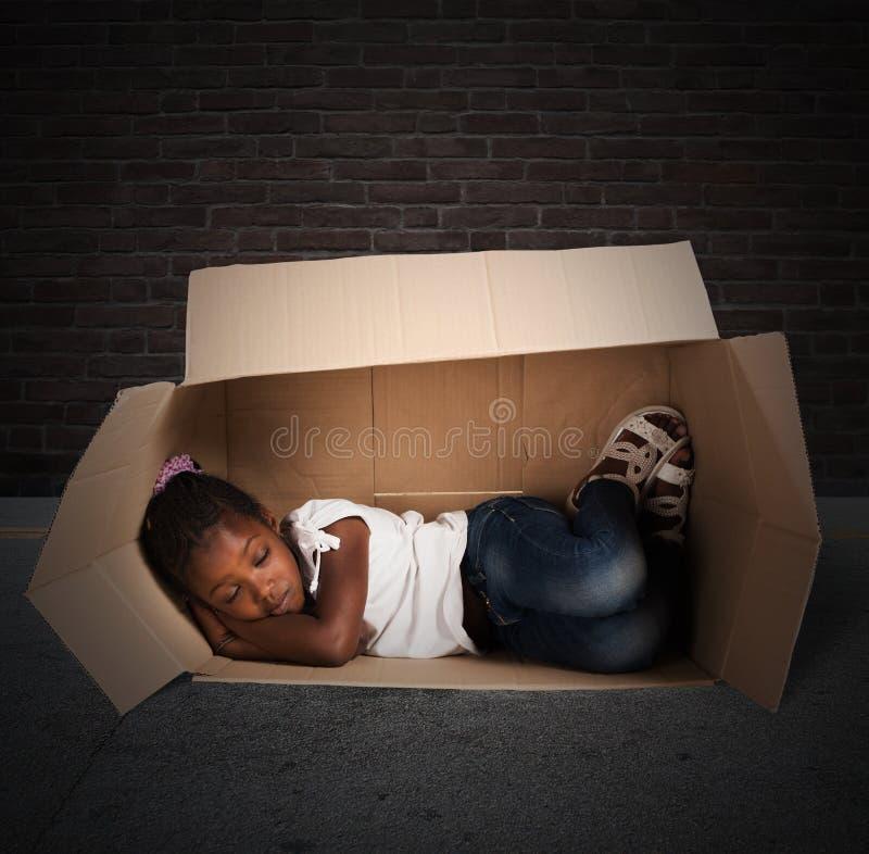 Poor child. Poor little girl sleeps in a cardboard royalty free stock image