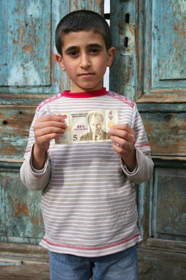 Poor child portrait. He is holding a 5 turkish liras banknote royalty free stock photo