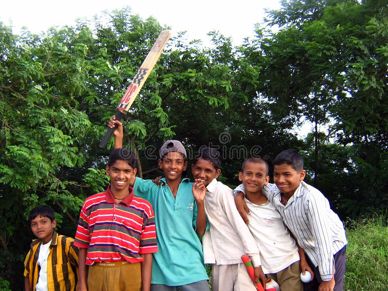 Poor Children. Pune India - Sept 25, 2006 : Poor Indian children posing with their cricket bat royalty free stock photos