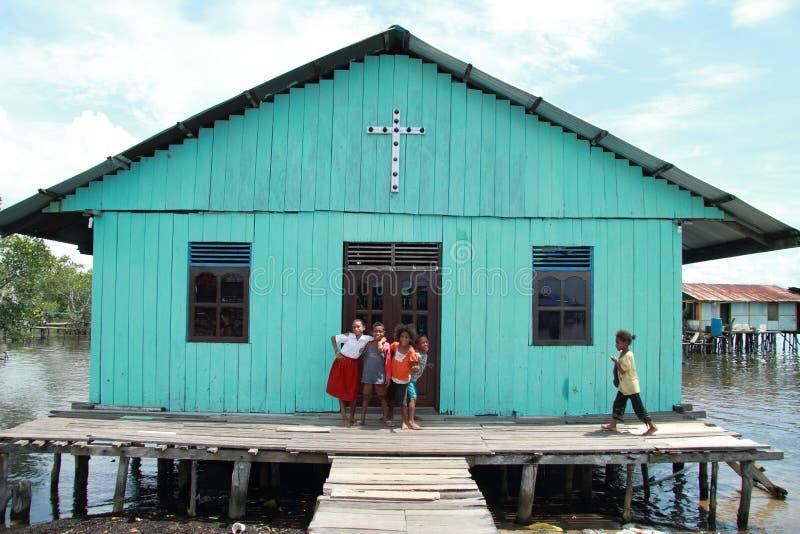 Poor children in front of church stock photo