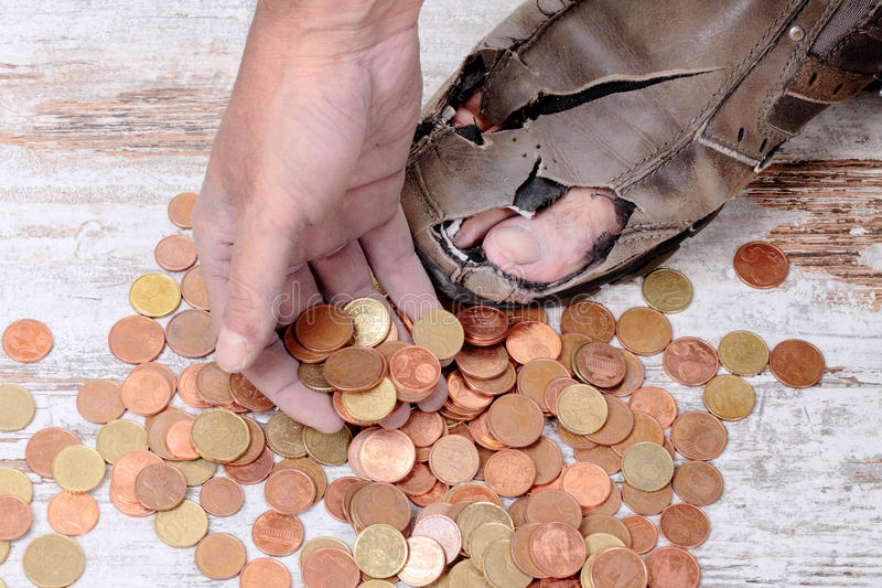 Poor and coins. A poor hands taking some coins stock image