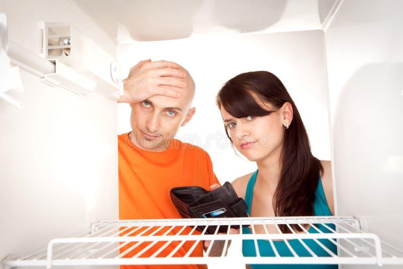 Poor couple looking in fridge. Poor couple with empty wallet looking in bare interior of empty modern refrigerator stock image