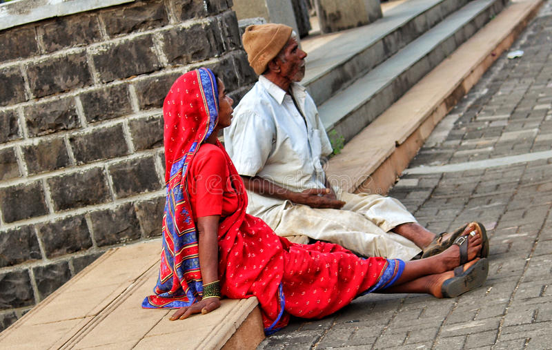 Poor couple on the street. A poor couple sitting on the streets of India stock photography