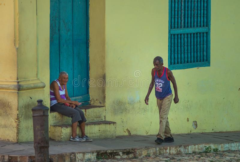 Poor Cuban old people capture portrait in traditional colorful alley with old colonial house, in old town, Cuba, America. royalty free stock images