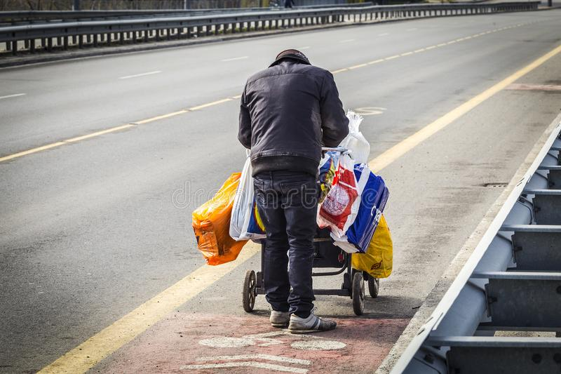 The homeless who dug in the trash to survive. poor lifestyle. Editorial use only. Burgas/Bulgaria/ 02.05.2018. A poor, dirty and torn person pushes a cart full stock photography