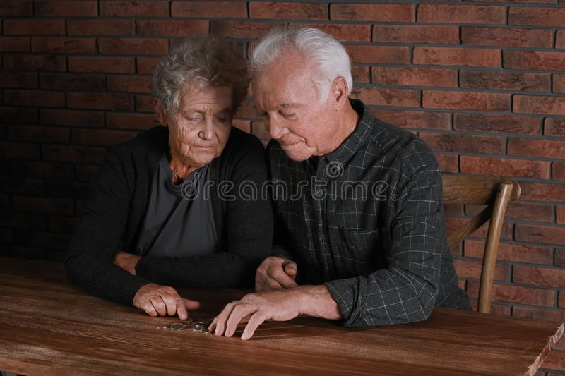 Poor elderly couple counting coins royalty free stock photo