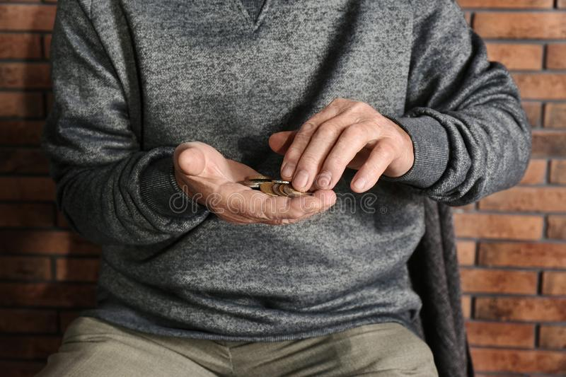 Poor elderly man counting coins stock photos