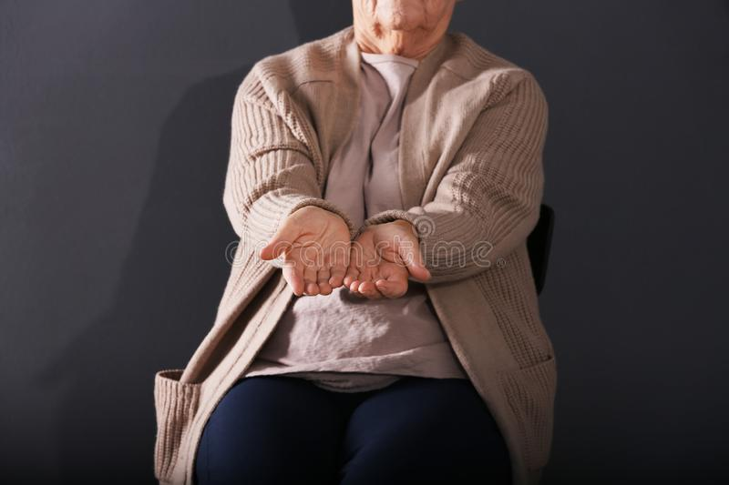Poor elderly woman begging for money on dark background. Focus on hands stock photos