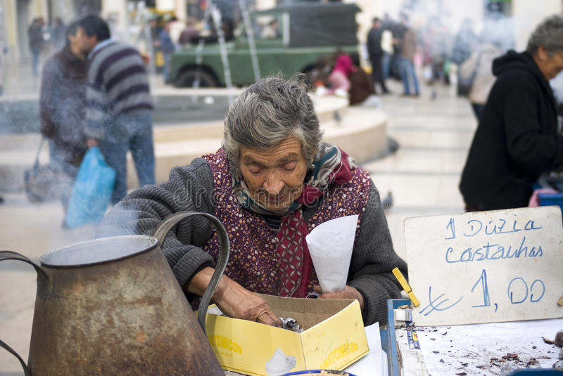 Poor elderly woman sells chestnuts. On the street of Coimbra, Portugal stock photography