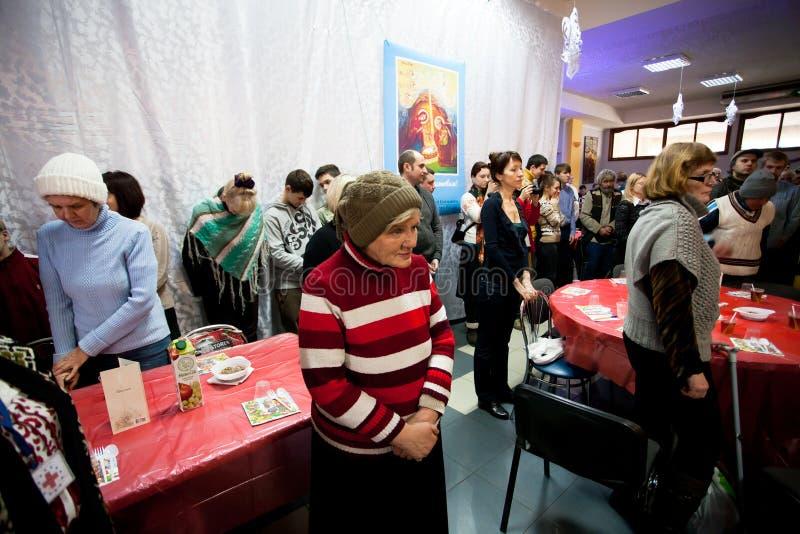 Poor elderly women and men pray before lunch at Christmas charity dinner for the homeless stock photo