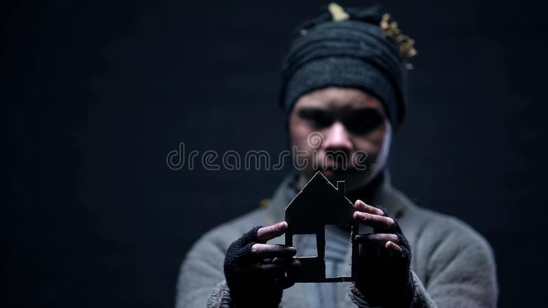 Poor emigrant holding paper house sign, dreaming about shelter, homelessness. Stock photo royalty free stock photos