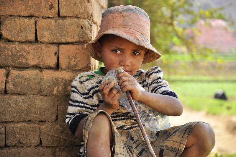Poor ethnic boy. Poor ethnic little boy sitting next to his house. Madagascar. Africa stock image