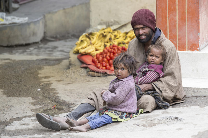 Poor family of beggars on the streets in India. LEH, INDIA - JUNE 29, 2015: Unidentified poor Indian beggar family on street in Ladakh. Children of the early stock photos