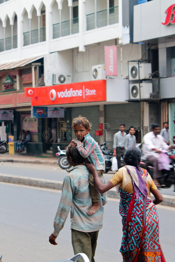 Poor family-India. Poor man roaming on road with his wife and son on shoulder. Ahmedabad, India royalty free stock photo