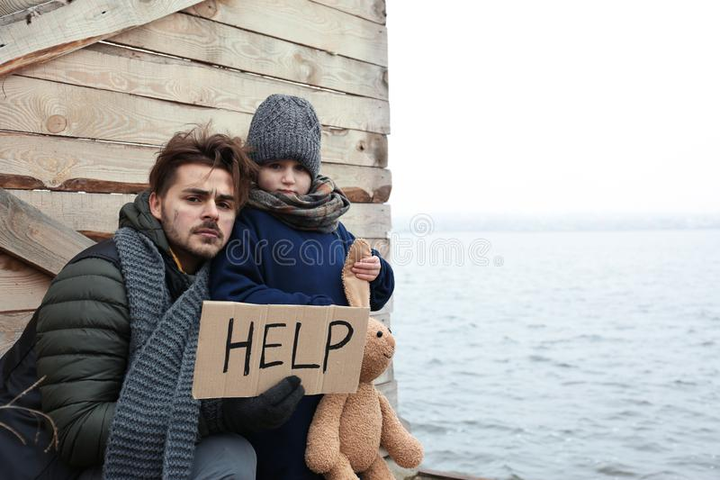 Poor father and child with HELP sign at riverside stock photos