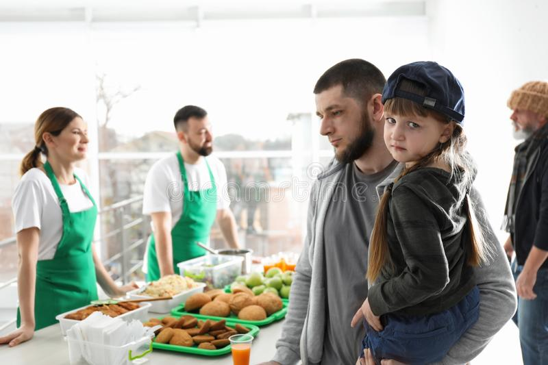 Poor father and daughter receiving food from volunteers stock image
