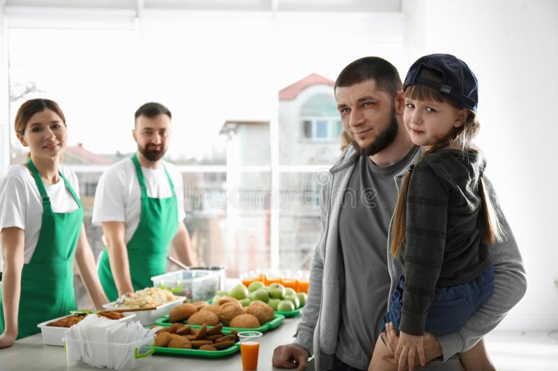 Poor father and daughter receiving food from volunteers stock images