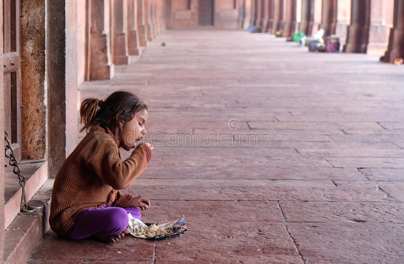 A poor girl eating in Fatehpur Sikri complex royalty free stock photos