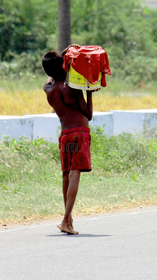 A Poor Homeless Boy Carrying drinking water. A Poor homeless boy is carrying drinking water in bucket from small pond for his family. And boy is covered on royalty free stock photos