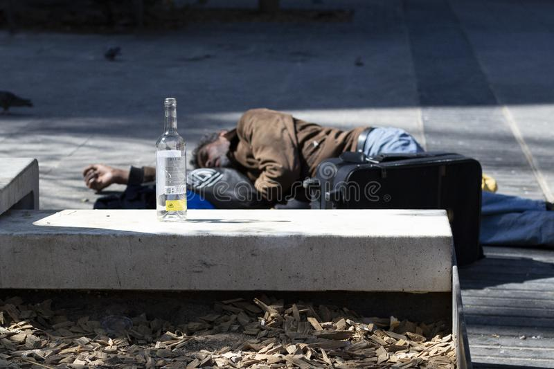 Poor homeless drunk man sleeping on the floor of the street on the background an empty bottle of wine. Barcelona stock images